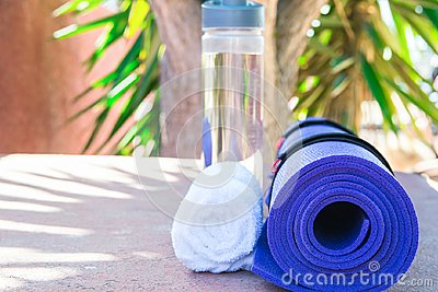 Blue Rolled Yoga Mat Bottle with Water White Towel on Greenery Palm Tree Nature Background. Sunlight. Relaxation Summer Meditation