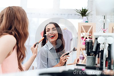 Girls do makeup in the showroom. Two beautiful girls have fun and smile.