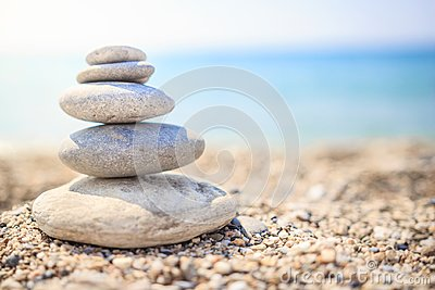 Stones are lined with pyramid on beach. Pebbles. Stones pyramid symbolizing zen, harmony
