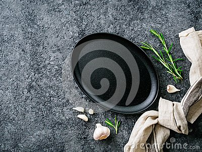 Empty oval cast iron frying pan on dark grey concrete background