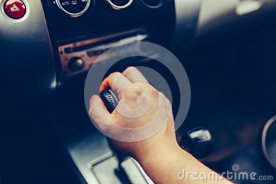 Man's hand switches automatic transmission closeup. Close up view of gear lever manual transmission car interior parts. Stylish T