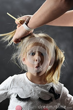 Little girl is very surprised when combing hair with female hands