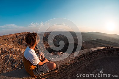 One person looking at the Fish River Canyon, scenic travel destination in Southern Namibia. Expansive view at sunset. Wanderlust t