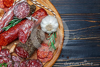 Various types of Dried organic salami sausage on wooden cutting board