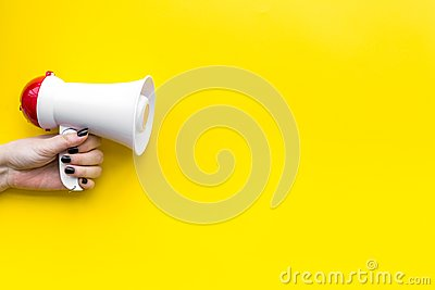 Attract attention concept. Megaphone in hand on yellow background top view copy space