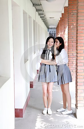 Two lovely Asian Chinese pretty girls wear student suit in school best friends smile laugh talking and gossip