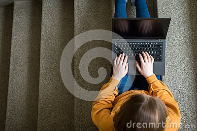 Young female college student sitting on stairs at school, writing essay on her laptop. Education concept.