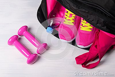 On the wooden floor sports bag with pink things in it uncovered, and two dumbbells