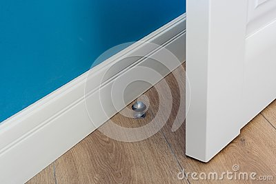 Close-up elements of the interior of the apartment. Metal chrome door stopper on laminate floor