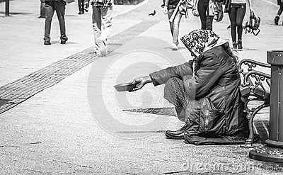 Hungry homeless beggar woman beg for money on the urban street in the city from people walking by, social documentary concept blac
