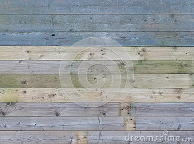 Colorful old rustic wooden plank wall or floor with some of the boards stained blue made of reused timber