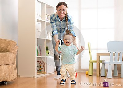 First steps of baby toddler boy learning to walk in white sunny living room. Footwear for child.