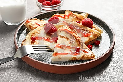 Thin pancakes served with syrup and berries