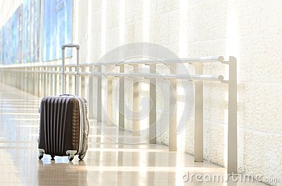 Packed travel suitcase, airport. Summer holiday and vacation concept. Traveler baggage, brown luggage in empty hall