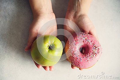 Young woman in white T-shirt choosing between green apple or junk food, donut. Healthy clean detox eating concept