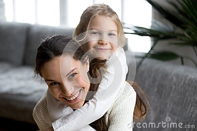 Happy single mother laughing piggybacking little girl daughter,