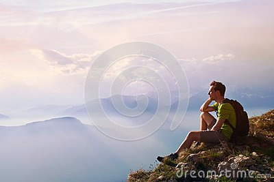 Man sitting on top of mountain, achievement or opportunity concept, hiker