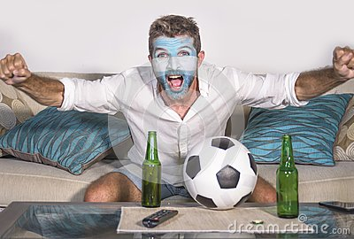 Young attractive man football supporter with Argentina flag painted face happy and excited watching cup match on TV celebrating vi