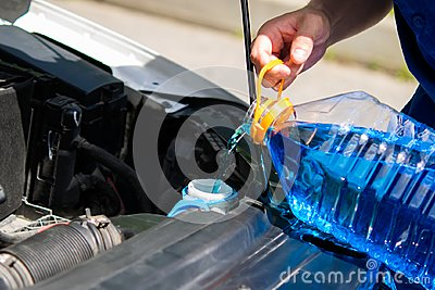 Service worker, pours in the tank washer fluid for washing car windows