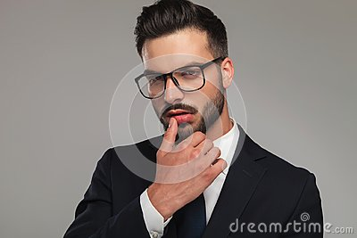 Sexy businessman flirting with thumb on lips