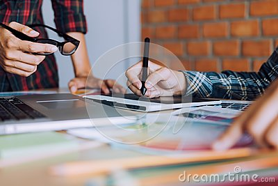 stock image of co-worker working with graphic design in office room together.