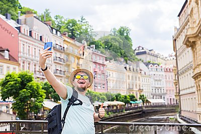 Handsome man taking selfie with mobile smart phone camera in european city. Vacation, travel and holiday concept.