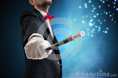 Magician or illusionist is showing magic trick. Blue stage light in background