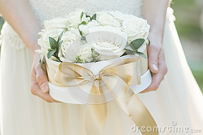 Bridesmaid holding a box of roses. Rose box. Beautiful gift with white roses.