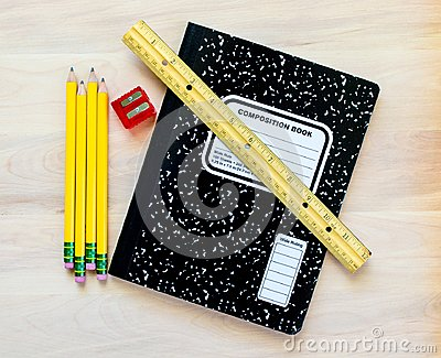 4 pencils, a pencil sharpener, a ruler and a notebook on a wooden desk