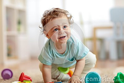 Cute infant baby crawling on the floor at home, playing with colorful toys