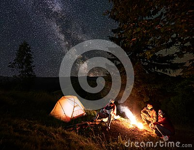 Two couples near campfire at night in the woods enjoying starry sky