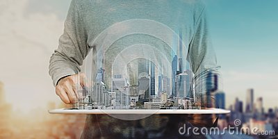 A man using digital tablet, and modern buildings hologram. Real estate business and building technology concept