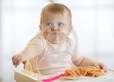 Adorable little baby one year eating pasta indoor. Funny toddler child with spaghetti. Cute kid and healthy food.