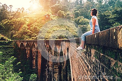 Woman sits on the Demodara nine arches bridge the most visited s