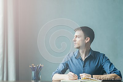 Young businessman caucasians sitting at desk office table and taking notes in notebook. Writing and looking out the window