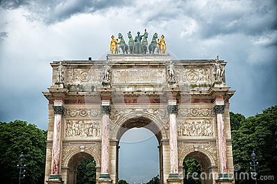 Arc de triomphe du carrousel in paris, france. Arch monument and green trees on cloudy sky. Architectural symbol of peace victory