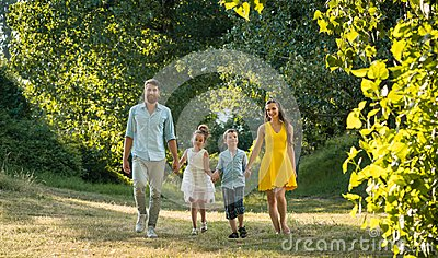 Happy family with two children holding hands during recreational walk in park
