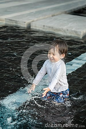 Closeup cute asian kid enjoy in swimming pool textured background in summer of thailand
