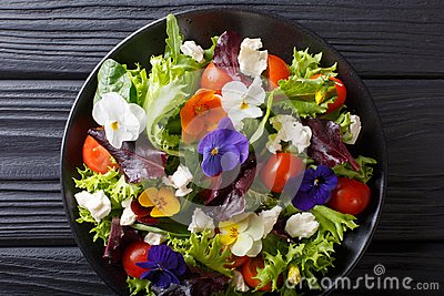 Mixed salad of edible flowers with lettuce, tomatoes and cream c