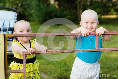 A little boy in a blue shirt and a girl in a yellow dress are standing behind an iron fence