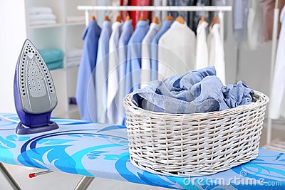 Wicker basket with clothes on ironing board