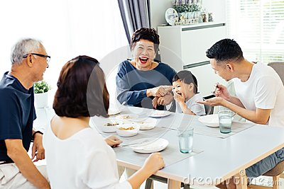 Happy Asian extended family having dinner at home full of laughter and happiness.