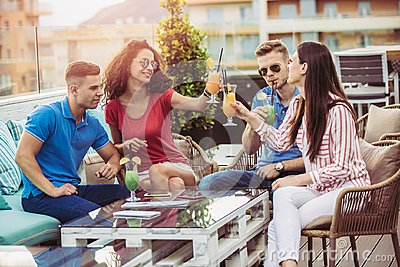 Friends drinking cocktails outdoor on a penthouse balcony