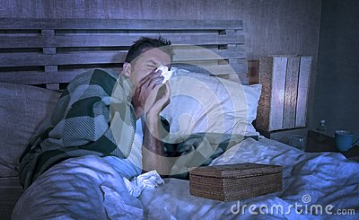 Wasted man sick at home freezing in bed covered with blanket sniffing sneezing and blowing nose suffering grippe feeling unwell