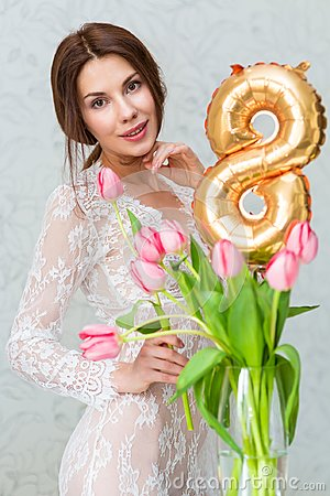 Beautiful young woman with spring tulips flowers bouquet. Happy girl smiling holds flowers, pink tulip. Spring portrait