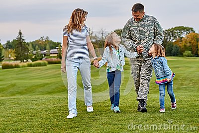 Happy family with soldier father walking outdoor.