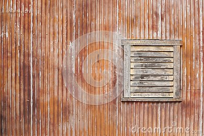 corrugated iron. A texture of corrugated rusty iron wall with wooden window.