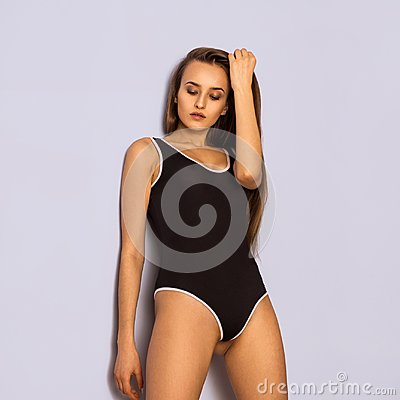 Pretty young girl in black body swimsuit