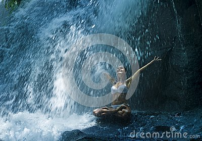 Attractive woman sitting at rock in yoga pose for spiritual relaxation serenity and meditation at stunning beautiful waterfall and