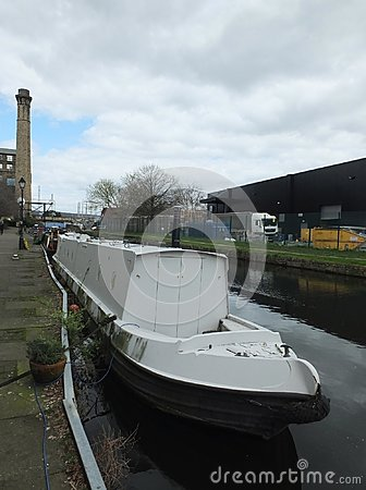 A white narrow boat moored on the canal in an industrial area of huddersfield with mill and bridge